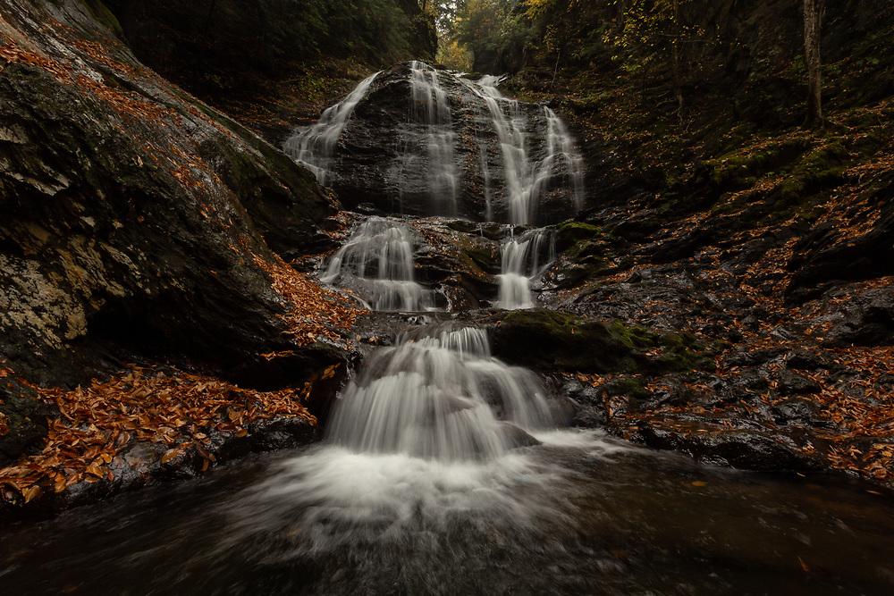 The descending cascades of Moss Glen Falls seen on a rainy autumn morning in Stowe.
