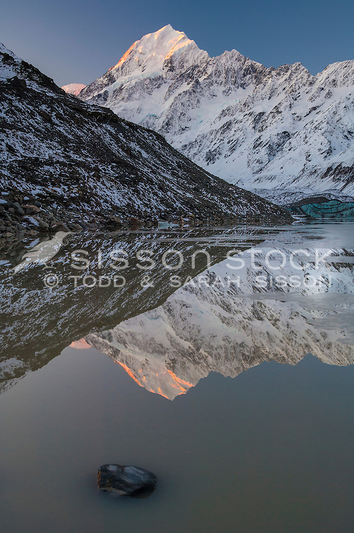 Aoraki Mt Cook & the Southern Alps reflected in Hooker Lake, at sunset.  Aoraki Mt Cook National Park, NZ.