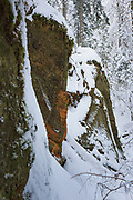 Two large sandstone cliff-faces next to small stream hidden in snow on snowy winter day, Gauja National Park (Gaujas Nacionālais parks), Latvia Ⓒ Davis Ulands   davisulands.com
