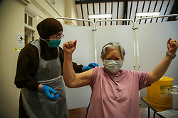 © Licensed to London News Pictures. 25/10/2021. London, UK.  74 year old Gulya Yoksenakool gestures after Nassima Larbi, a NHS vaccinator, administered the Pfizer/BioNTech Covid-19 booster vaccine at a vaccination centre in north London. Ministers are urging those eligible to get a Covid-19 vaccine and booster jab this winter amid fears of further restrictions as coronavirus infection cases rise. The Government is considering cutting the interval between booster jabs and the second dose of a Covid-19 vaccine from six to five months. Photo credit: Dinendra Haria/LNP