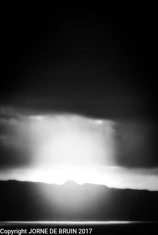 During a rainstorm over the sea, spectacular light filters through the clouds above the Isle of Skye.