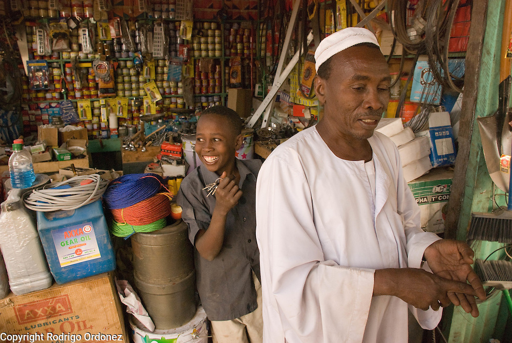 """Trader Mohammed Abdulrahman, from El Muglad (right), owns a hardware store in the market of Abyei. Recent developments in Abyei town are making people settle down. """"No one was thinking of using these materials before."""""""