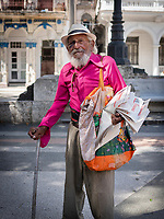 Smiling old man with a cane and wearing a bright pink shirt selling newspapers in Havana.