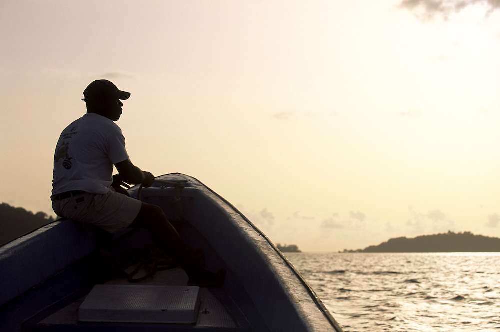 One of the skippers of Bom Bom resort, looks at Bom Bom isle in the distance at sunset.