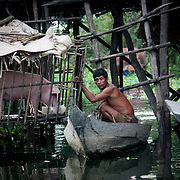 Fishing village man in canoe checks pig cage (Siem Reap, Cambodia - Oct. 2008) (Image ID: 081023-1700551a)