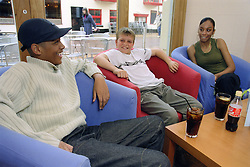 Group of young people sitting around table in bar talking and laughing,