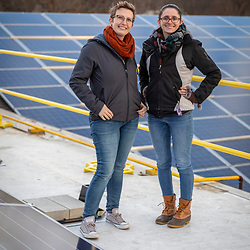 PV Squared employees Rachel Levy (left) and Anna Mannello at a solar panel installation on the roof of a commercial building in Greenfield, Massachusetts.