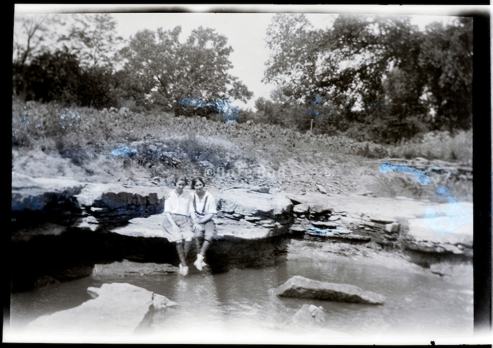 friends sitting by water edge damaged vintage photo