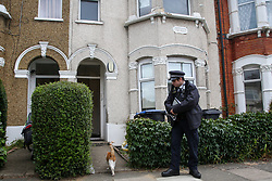 © Licensed to London News Pictures. 28/07/2021. London, UK. A neighbours cat walks past a police officer guarding a residential property on Stanley Road in Enfield, north London. Police officers responded to calls of concern relating to the address on Stanley Road in Enfield, at approximately 16:00hrs on 27 July and found a man in his 40s dead. A woman has been arrested and is believed to have known the man. Photo credit: Dinendra Haria/LNP