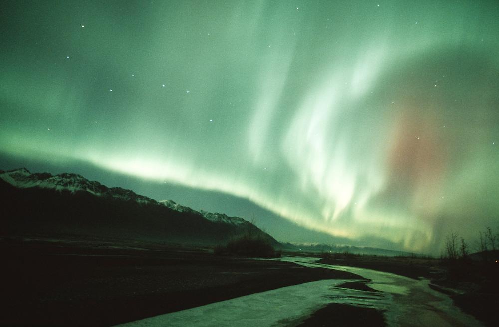 Palmer, Alaska. Aurora Borealis or northern lights abover knik River and Chugach Mnts.