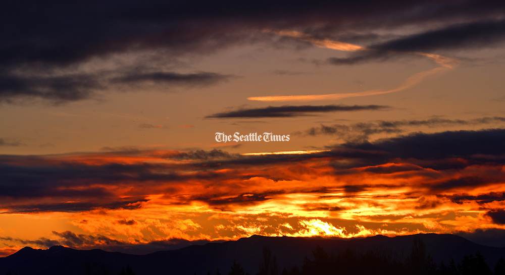 The Cascade Mountain range loom in front of Thursday morning's sunrise in this view from SeaTac, Washington. (Mike Siegel / The Seattle Times)