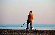 An elderly man dressed in a winter coat and hat beach combing with a metal detector and a spade on Folkestone Beach, United Kingdom, 19th January 2016