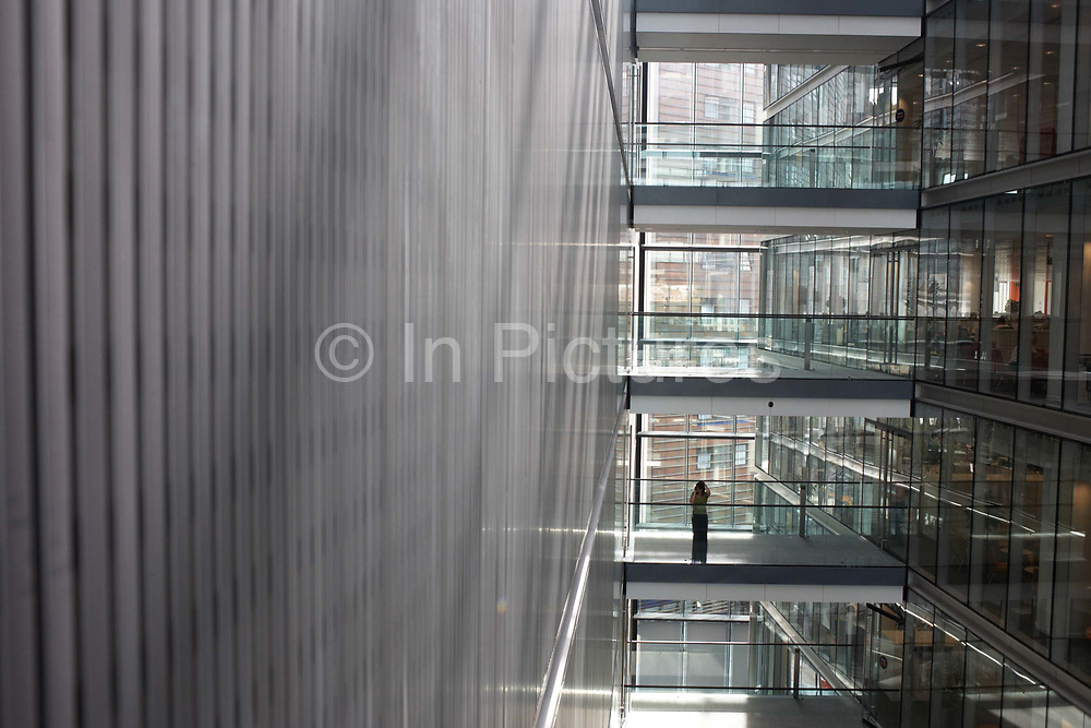 A female office worker pauses to make a call on her mobile phone, on a wide walkway in Ernst & Young's Norman Foster-designed 385,000 square foot European headquarter at More London, London England. All other walkways above and below are empty and holding her head, the lady has sought privacy from her open-plan workstation and stands on her own. Architecturally, the term atrium comes from Latin: A large and light central hall or reception of a house where guests were greeted. The depth and height of all levels from near the top to almost the bottom give a sense of vertigo, a dizzying perspective. E & Y employs 114,000 people, in 700 locations across 140 countries around the world.