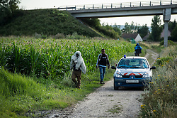 © London News Pictures. Calais, France. French police drive past a group of immigrants walking near the Eurotunnel complex. Migrants attempting to reach the UK via the Eurotunnel at Calais in France. The situation has reached crisis point, which French police over run by attempts to cross the border. Photo credit: Ben Cawthra /LNP