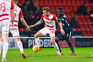 James Coppinger of Doncaster Rovers (26) holds the ball up with Elvis Bwomono of Southend United (2) at his back during the EFL Sky Bet League 1 match between Doncaster Rovers and Southend United at the Keepmoat Stadium, Doncaster, England on 12 February 2019.