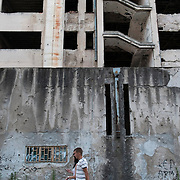 MOSTAR, BOSNIA AND HERZEGOVINA - JUNE 28:  A couple walks in front of a building damaged by bulletts from the 1993 war on June 28, 2013 in Mostar, Bosnia and Herzegovina. The Siege of Mostar reached its peak and more cruent time during 1993. Initially, it involved the Croatian Defence Council (HVO) and the 4th Corps of the ARBiH fighting against the Yugoslav People's Army (JNA) later Croats and Muslim Bosnian began to fight amongst each other, it ended with Bosnia and Herzegovina declaring independence from Yugoslavia.  (Photo by Marco Secchi/Getty Images)