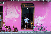 A shopkeeper mops the entrance to his furniture store specializing in traditional Poltrona style wooden rocking chairs in Tlacotalpan, Veracruz, Mexico. The tiny town is painted a riot of colors and home to legendary Mexican musician Agustín Lara.