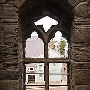 A window looking out towards the town at Caernarfon Castle in northwest Wales. A castle originally stood on the site dating back to the late 11th century, but in the late 13th century King Edward I commissioned a new structure that stands to this day. It has distinctive towers and is one of the best preserved of the series of castles Edward I commissioned.