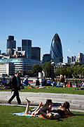 Scenes of both tourists and local office workers sunbathing on the grass at the park near to Tower Bridge. Here the Cityof London including the Gherkin are over the river.