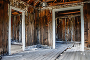 "Dilapidated doors in a ramshackle building at Bodie, California's official state gold rush ghost town. Bodie State Historic Park lies in the Bodie Hills east of the Sierra Nevada mountain range in Mono County, near Bridgeport, California, USA. After W. S. Bodey's original gold discovery in 1859, profitable gold ore discoveries in 1876 and 1878 transformed ""Bodie"" from an isolated mining camp to a Wild West boomtown. By 1879, Bodie had a population of 5000-7000 people with 2000 buildings. At its peak, 65 saloons lined Main Street, which was a mile long. Bodie declined rapidly 1912-1917 and the last mine closed in 1942. Bodie became a National Historic Landmark in 1961 and Bodie State Historic Park in 1962."