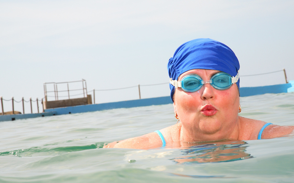 eldrely Lady kissing into the lens while swimming in a pool