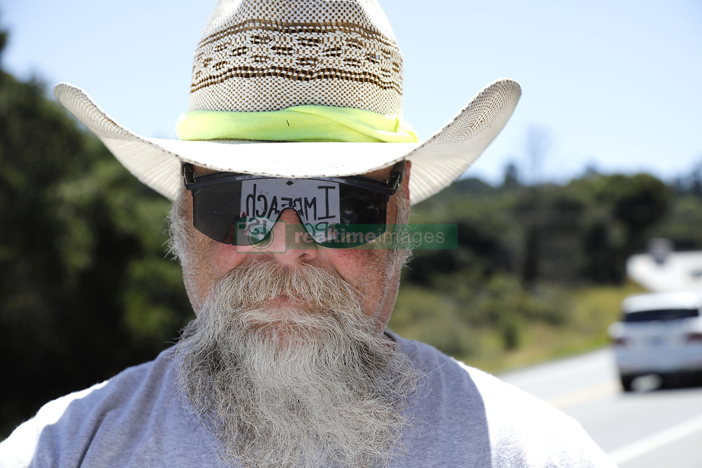 July 3, 2017 - Royal Oaks, CA, USA - Mark Sleeper of Royal Oaks, CA holds a sign reflected in his sunglasses advising drivers on San Miguel Canyon Road to ''Please Impeach'' or ''Impeach POTUS'' as they drive in either direction.  Sleeper, who voluntarily cleans both sides of this road was in the Navy during the Vietnam Era aboard the USS Midway and is not supportive of Donald Trump. ''Trump is not president material,''  he said. (Credit Image: © John Gastaldo via ZUMA Wire)
