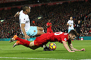 Adam Lallana of Liverpool goes down from a challenge from  Dimitri Payet of West Ham United. Premier League match, Liverpool v West Ham Utd at the Anfield stadium in Liverpool, Merseyside on Sunday 11th December 2016.<br /> pic by Chris Stading, Andrew Orchard sports photography.