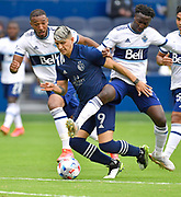 May 16, 2021 - Kansas City, KS, United States:  Sporting Kansas City forward Alan Pulido (9, center) finds himself sandwiched between Vancouver Whitecaps defender Derek Cornelius (13, left) and Vancouver Whitecaps midfielder Janio Bikel (19) as he moves towards the Vancouver goal.   Sporting KC beat the Vancouver Whitecaps FC 3-0 in a Major League Soccer game. <br /> Photo by Tim Vizer/Polaris