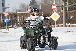 Girl riding quad bike on snow covered road