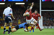 Alex Cuthbert of Wales is tackled by Agustin Ormaechea of Uruguay. Rugby World Cup 2015 pool A match, Wales v Uruguay at the Millennium Stadium in Cardiff, South Wales  on Sunday 20th September 2015.<br /> pic by  Andrew Orchard, Andrew Orchard sports photography.