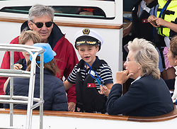 Prince George, with missing front teeth and wearing a Captain's cap, and Michael Middleton watch the inaugural King's Cup regatta, hosted by the Duke and Duchess of Cambridge, in Cowes, Isle of Wight on August 8, 2019.