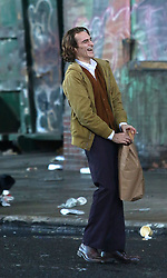 """Joaquin Phoenix is pictured for the first time playing the title role for the upcoming """"JOKER"""" movie in which he lost a lot of weight to play the part. The movie takes place on a 1980s gritty New York City. The movie was being filmed in Manhattan's Harlem area. At one point during a scene that required him to kick stuff around he hurt his foot and was seen carrying a bag of ice. 16 Sep 2018 Pictured: Joaquin Phoenix. Photo credit: LRNYC / MEGA TheMegaAgency.com +1 888 505 6342"""