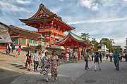 Tourists, some dressed in traditional Japanese kimono, wander around the main shrine at Fushimi Inari
