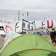 """A family of refugees standing right next to the fence build by the FYR Macedonian Police and a banner writing """"Made in EU"""" Transit camp of Idomeni, Greece. <br /> <br /> Thousands of refugees are stranded in Idomeni unable to cross the border. The facilities are stretched to the limit and the conditions are appalling."""