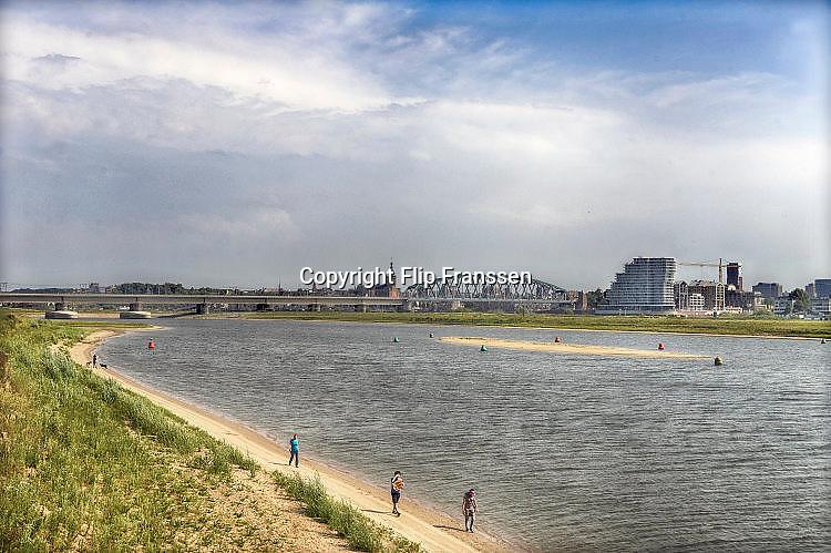 Nederland, Nijmegen, 15-6-2017 De bijna 4 km. lange nevengeul van de Waal bij Lent. Grootste onderdeel van de vele werken van Rijkswaterstaat om bij hoogwater een betere waterafvoer in de rivier te hebben. Het dorp veurlent is op een kunstmatig eiland komen te liggen met twee kleinere bruggen als ontsluiting. Wandelaars in het recreatiegebied. Ruimte voor de rivier, water, waal. In de nieuwe dijk wordt een drempel gebouwd die stapsgewijs water doorlaat en bij hoogwater overloopt. The Netherlands, Nijmegen Measures taken by Nijmegen to give the river Waal, Rhine, more space to flow during highwater and to prevent the risk of flooding. Room for the river. Reducing the level, waterlevel. Large project to create a new paralel gully, an extra flow of water, so the river can drain more water during highwater. Due to climate change and expected rise, increase of the sealevel, the Dutch continue to protect their land from the water. Foto: Flip Franssen