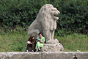 """North Korean women read together next to a stone lion along the river port town of Sinuiju July 8, 2006. China and North Korea are separated by the Yalu River, upon which Chinese tourists take pleaure cruises across the water to  observe their less economically developed neighbors.  North Korea has threatened to take """"stronger physical actions"""" after Japan imposed punitive measures in response to its barrage of missile tests and pushed for international sanctions. North Korea has vowed to carry out more launches and has said it will use force if the international community tries to stop it. DPRK, north korea, china, dandong, border, liaoning, democratic, people's, rebiblic, of, korea, nuclear, test, rice, japan, arms, race, weapons, stalinist, communist, kin jong il"""