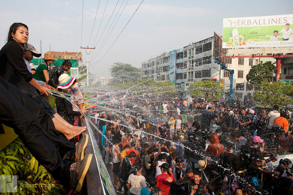Mandalay, Myanmar- April 14, 2013: High atop the water platforms, celebrants aim hoses at some of the thousands of young people who pour into the streets of Mandalay to dance and get hosed by water during Myanmar's Thingyan Water Festival. Thingyan is held in April, one of the hottest months of the year in Myanmar. The water festival marks the country's New Year celebration and the festival includes lots of drinking, singing, dancing and theater. Wherever you are you are likely to get doused with water as the Burmese see this as a cleansing of the previous year's sins and bad luck and a blessing for good luck and prosperity in the year ahead. In the major cities of Mandalay and Yangon, large platforms are erected along major roadways and are equipped with high powered water hoses. The platforms, sponsored by large corporate donors, also have dance stages and play the latest pop and hip hop music. Thousands of residents pour into the streets by foot, motorbike and flatbed truck to get hosed under the platforms while they drink and dance. Many of the young celebrants wear their best clubbing clothes. And many of the party goers are men, having left their wives and girlfriends at home.