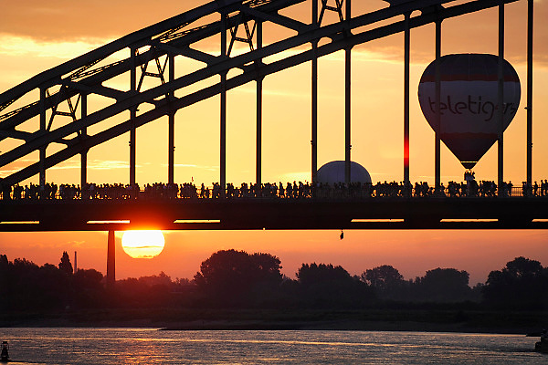 Nederland, Nijmegen, 21-7-2009Het is weer zover. Deelnemers aan de 4daagse, vierdaagse,  lopen over de waalbrug richting Elst op de eerste dag van de 93e editie van dit wandelevenement.Foto: Flip Franssen/Hollandse Hoogte The International Four Day Marches Nijmegen (or Vierdaagse) is the largest marching event in the world. It is organized every year in Nijmegen mid-July as a means of promoting sport and exercise. Participants walk 30, 40 or 50 kilometers daily, and on completion, receive a royally approved medal (Vierdaagsekruis). The participants are mostly civilians, but there are also a few thousand military participants. In 2004 a restriction on the maximum number of registrations is set for the first time. The maximum number of 47,000 registrations then has been reached within 6 weeks. More than a hundred countries have been represented in the Marches over the years.The 90th Four Days Marches were very special. After one participant had died during the march and another after finishing the first walking day and a large amount of the walkers had needed help with heat-related problems during the march, the Four Days Marches were cancelled after one day.Foto: Flip Franssen/Hollandse Hoogte
