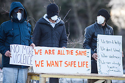 © London News Pictures. Calais, France. 07/03/16. Refugees stand in silent protest as French police enter the 'Jungle' camp to begin the second week of the demolition. French authorities are evicting and demolishing the southern half of the Calais 'Jungle' camp, which charities estimate to contain 3,500 people. . Photo credit: Rob Pinney/LNP