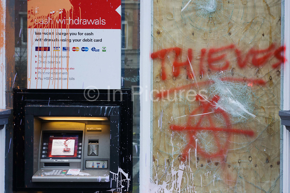 Vandalism to an HSBC bank cash dispenser the morning after the TUC-organised anti-government cuts to Britain's economy. The word Thieves has been sprayed with aerosol on a boarded-up window relating to the belief by protesters that HSBC is a tax-evader. The riot by anarchists who broke away from a largely peaceful protest agasinst government economic cuts. Organisers estimated between 250,000 and 500,000 people took part but police said a total of 201 arrests had been made during the day largely for a variety of public order offences, they said. In addition, 66 people were reported to have been injured, including at least 31 police officers, 11 of whom required hospital treatment.