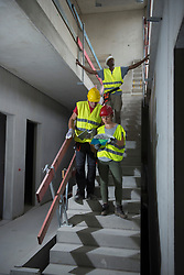 Construction workers with architectural plan at building site, Munich, Bavaria, Germany