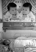 """China's Aging Population 11 - An ederly patient sleeps beneath a poster depicting baby twins and the slogan """"Healthy Long Life."""""""