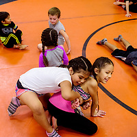 Mya Baca, left, tries new moves on Anastasia Dedman during the Gallup Wrestling Camp at Gallup High School Thursday.