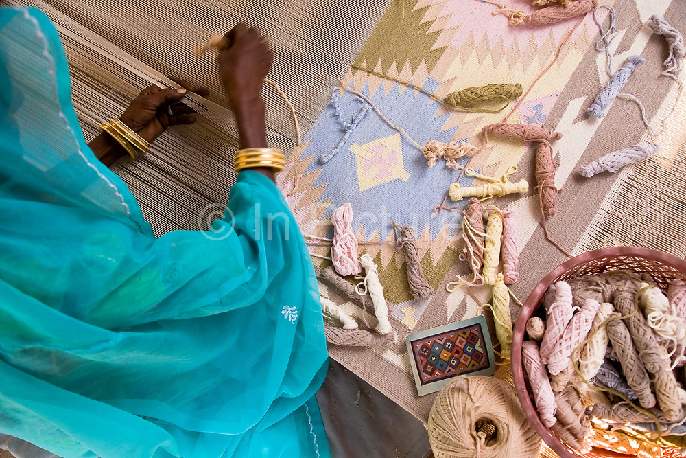 A Indian woman weaves a dhurrie on a traditional loom using a typical geometric pattern using a interlocking technique, Salawas, Rajasthan, India.