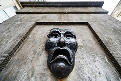 Theatrical mask bronze relief with sad face on High Street Wellhead on the Royal Mile in Edinburgh, Scotland, UK to indicate sadness of cancellation of the Edinburgh Fringe festival 2020.