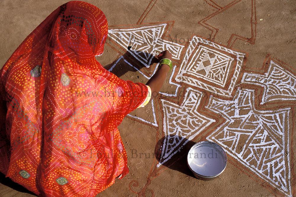 Inde - Rajasthan - Village des environs de Tonk - Femme réalisant des peintures au sol (Mandana)