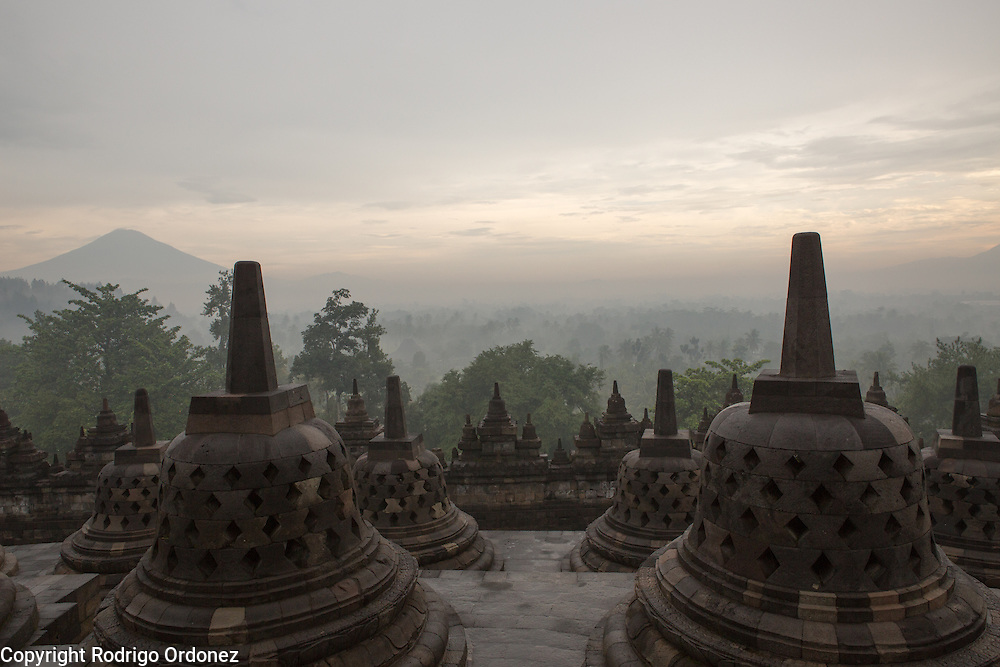 View from atop Borobudur temple at sunrise, featuring volcanoes and the landscape of Central Java, Indonesia. The top platform has 72 perforated stupas with seated Buddha statues inside.