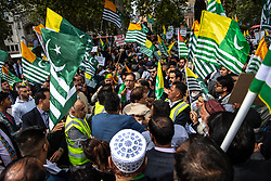 © Licensed to London News Pictures. 03/09/2019, London, UK. Pakistani flags are draped over the the statue of Mahatma Gandhi in Westminster as pro Pakistani demonstrators rally in Parliament Square over the continuing crisis in Kashmir. Photo credit: Guilhem Baker/LNP.