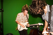 Tom Beecham, frontman of The Raggedy Anns, rocks out with guitarist Hamilton Boyce of Song Sparrow Research at an underground music venue in Seattle, Washington.