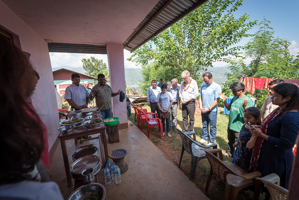 17 September 2018, Biruwa, Kavre district, Nepal: Rev. Joseph Soren from Nepal Evangelical Lutheran Church blesses the food before the meal starts. What may appear an ordinary lunch is in fact quite special. As Dalits find themselves among the most marginalized in Nepal society, members of other castes will often not receive food from them even if offered. Today, however, a range of visitors, including local authority officials sit and eat with them, to affirm the equality and dignity of all people, no matter their ethnic group, economic situation, or caste. The Lutheran World Federation World Service programme runs a Post-Earthquake Rehabilitation and Livelihood Recovery Project, in which Biruwa is one of the supported communities.